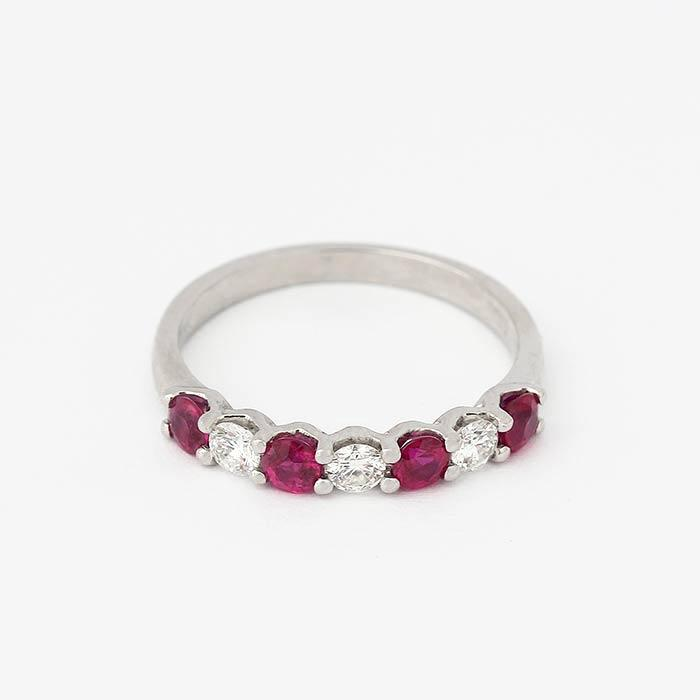 ruby and diamond half eternity ring with 7 round stones in a claw setting and in platinum