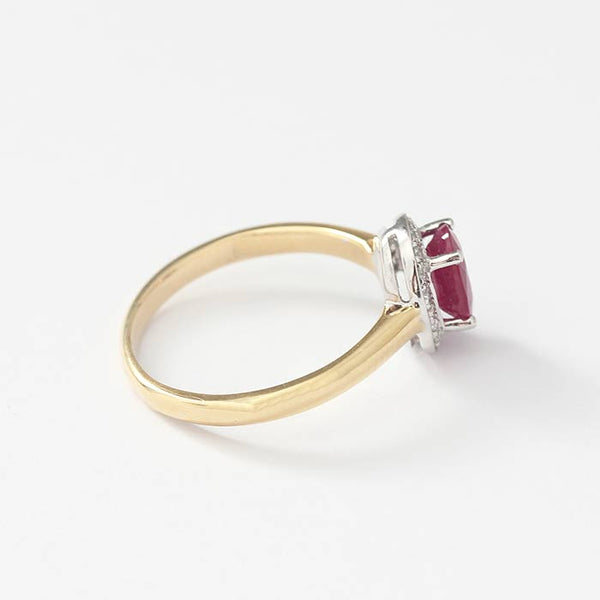 a ruby and diamond cluster ring with yellow gold band and white setting