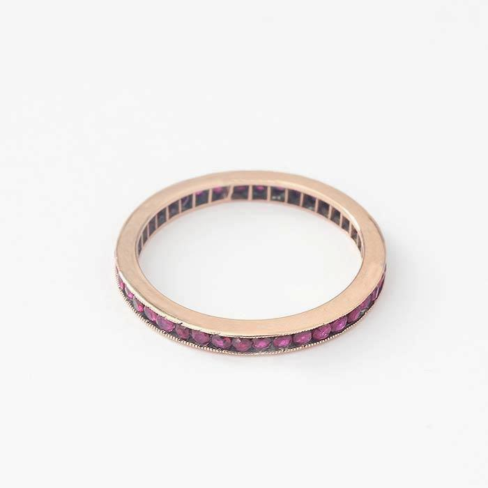 a full eternity ring made in rose gold with small round faceted rubies in a channel setting