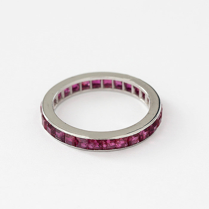 a ruby set full eternity ring in platinum with square stones in a channel setting