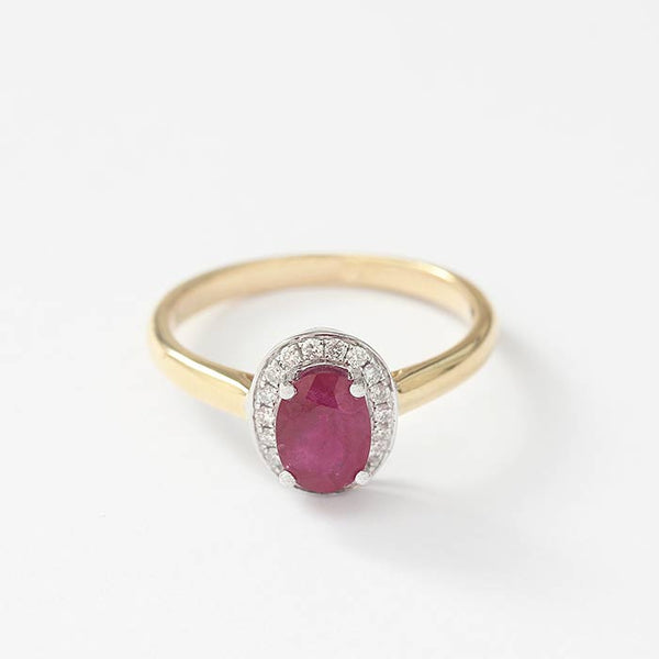 a ruby and diamond ring with a central oval ruby and a surround of diamonds in a claw setting