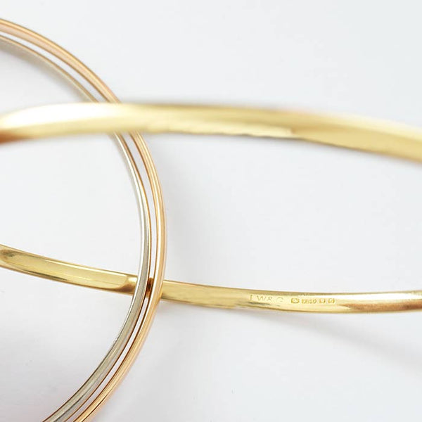 a yellow white and rose gold solid russian bangle with hallmark