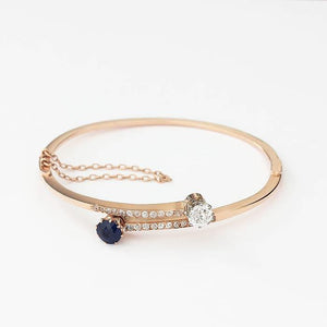 a secondhand rose gold sapphire and diamond cross over design bangle with safety chain