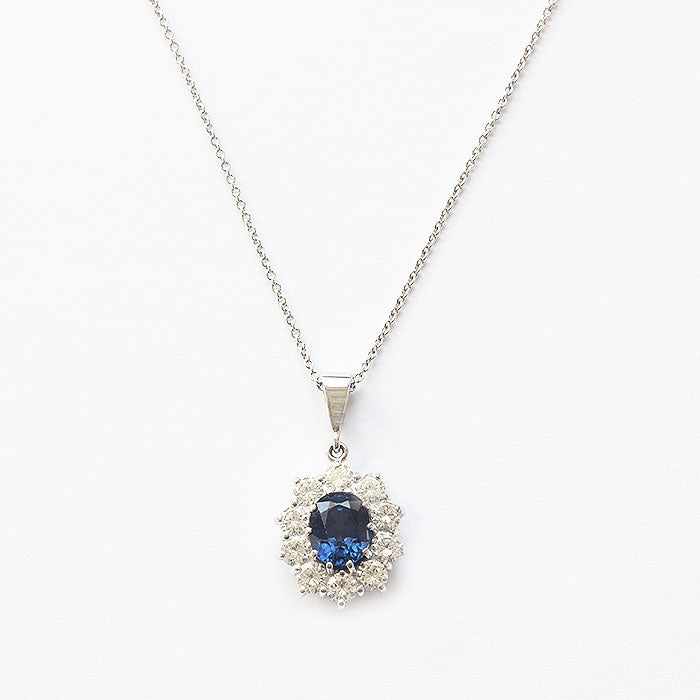 a sapphire diamond oval cluster pendant with trace chain all in white gold