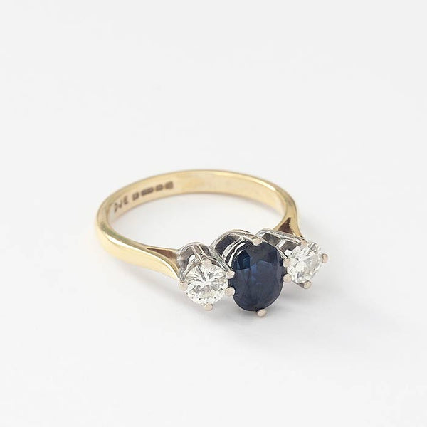 an oval sapphire and 2 round diamonds in a white gold claw setting with yellow gold band hallmarked 1976