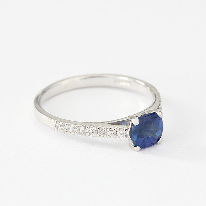 cushion cut blue sapphire ring with diamond shoulders and a white gold band