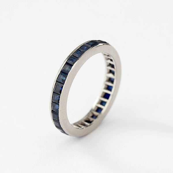 a sapphire full eternity ring in white gold and a channel setting