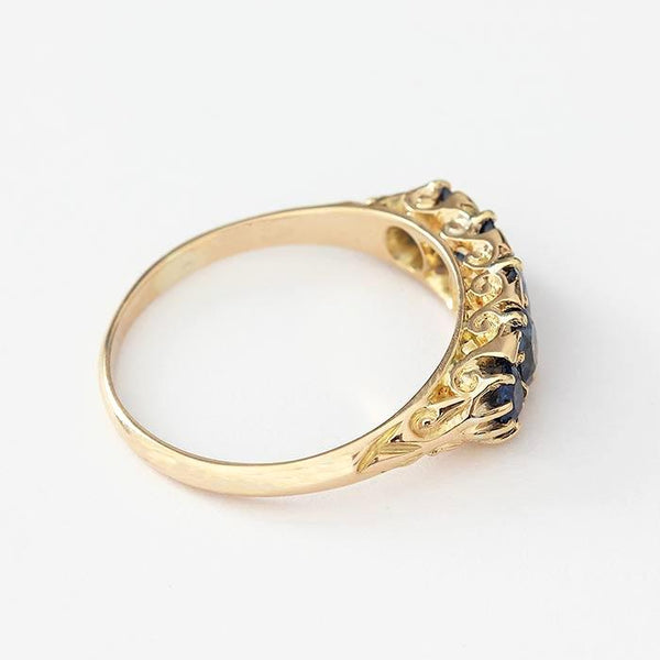 a vintage sapphire graduated 5 stone ring with carved scroll sides and shoulders all in yellow gold