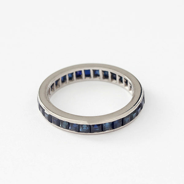 a full eternity ring with square sapphires in a channel setting and white metal mount