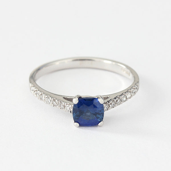 cushion shaped blue sapphire in a claw setting with diamonds in the shoulders the ring is 18ct white