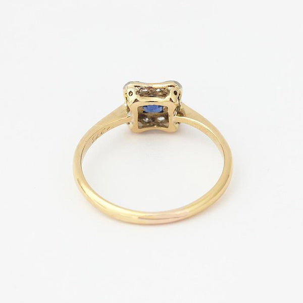 a preowned sapphire and diamond cluster ring in yellow gold with central sapphire