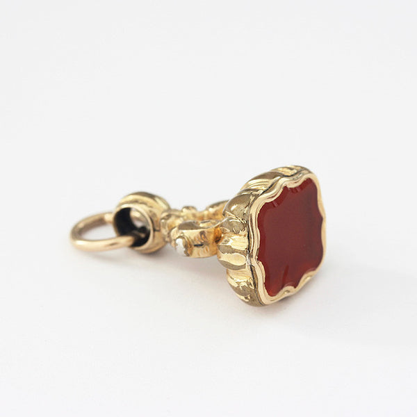 a plain gold plated seal fob charm with pattern on the edges