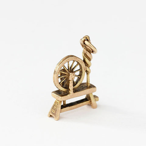 spinning wheel charm in yellow gold