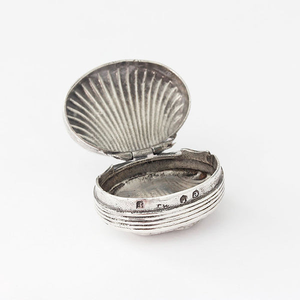 a small silver snuff pot with a shell pattern
