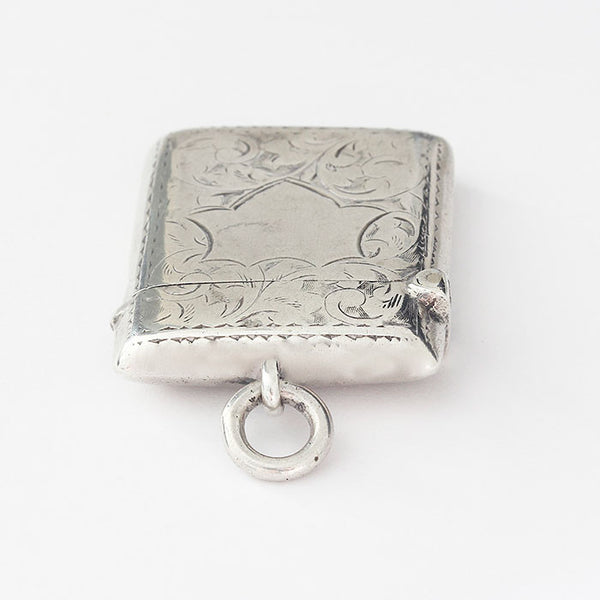 silver vesta case with rectangle shape floral pattern and shield