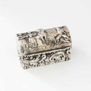 a silver antique 3 ring box with figurines and buildings embossed outside and hallmarked 1912