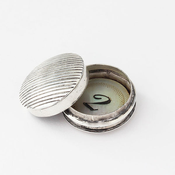 a small silver pot with little gaming counters inside
