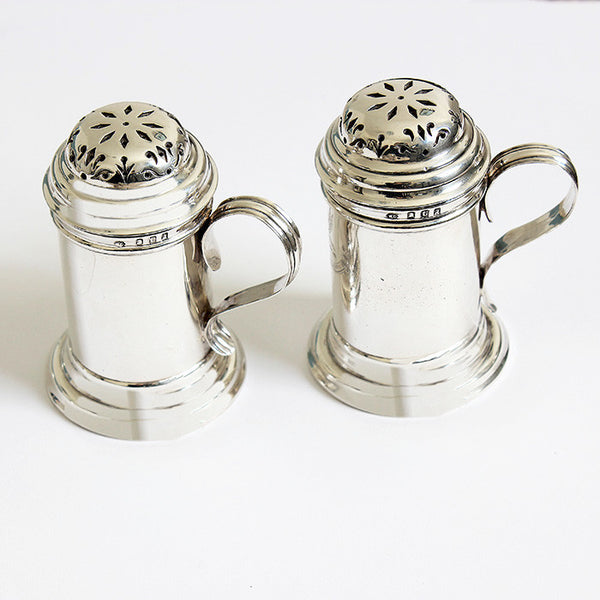 a silver pair of britannia peppers with a family crest and motto on the side with a full hallmark