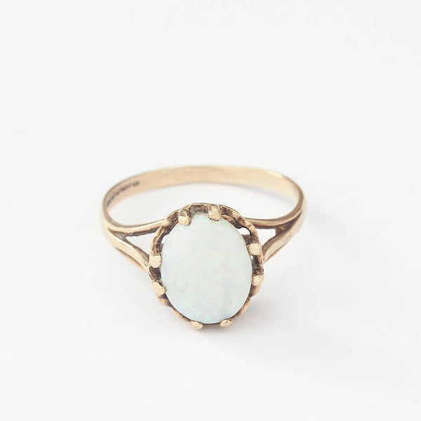 a secondhand yellow gold claw set opal ring with a cabochon oval stone with multi claws
