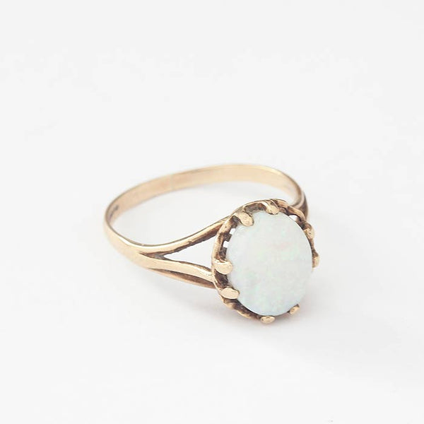 a single stone opal ring in yellow gold with a multi claw setting