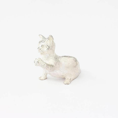 a sterling silver sitting cat with playful paw ornament
