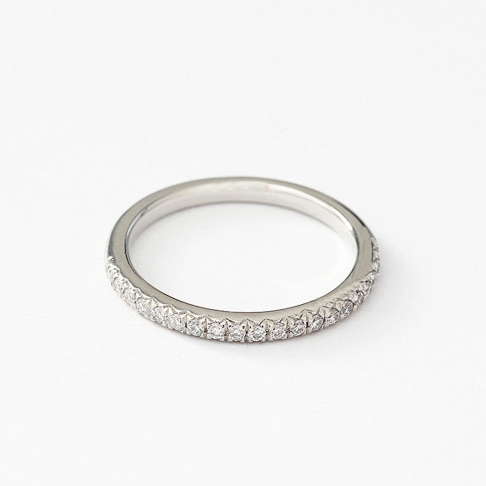 a platinum eternity ring in half set with diamonds in a channel claw setting