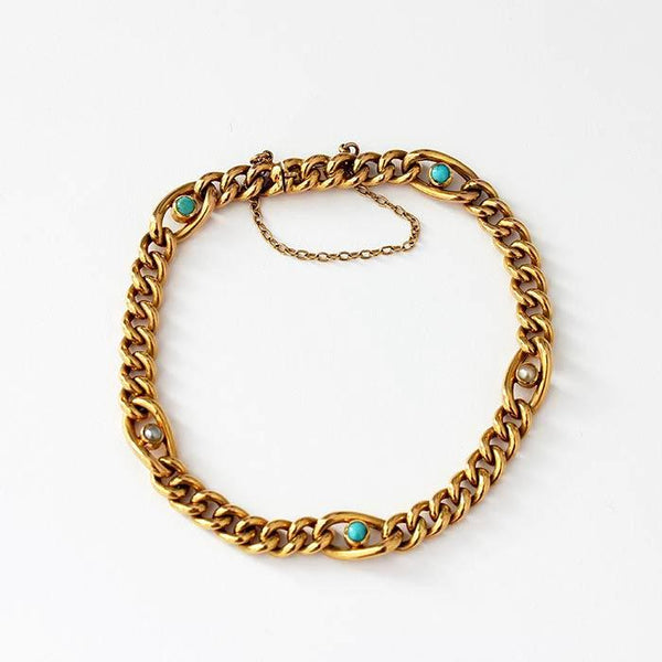 a turquoise and pearl bracelet with a curb link section in between and a safety chain all in yellow gold vintage style