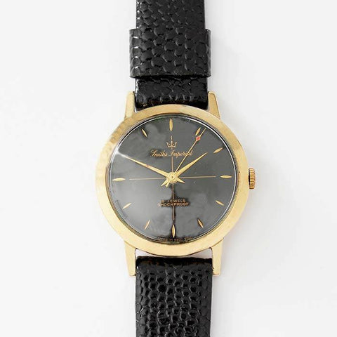 a smiths imperial 9 carat gold cased watch with leather strap and black dial with gold colour batons