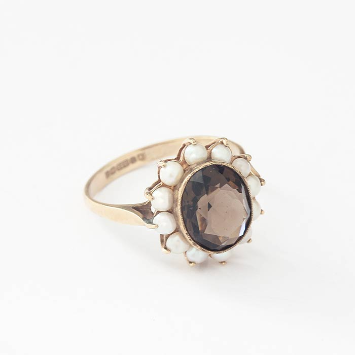 a faceted oval smokey quartz stone with a pearl surround in a claw setting with a yellow gold band