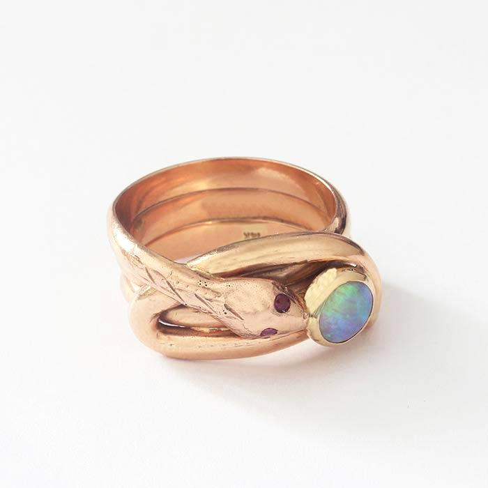 a snake design ring in 3 rows with a round cabochon opal stone and ruby set eyes secondhand