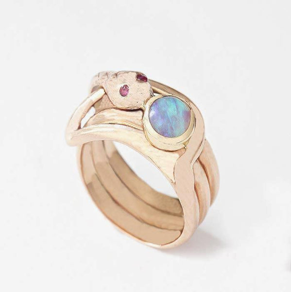 a secondhand gold 3 row snake design ring with ruby set eyes and a single round opal