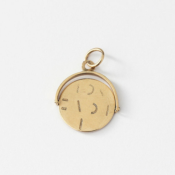 a yellow gold charm with a spinning design and i love you words appear