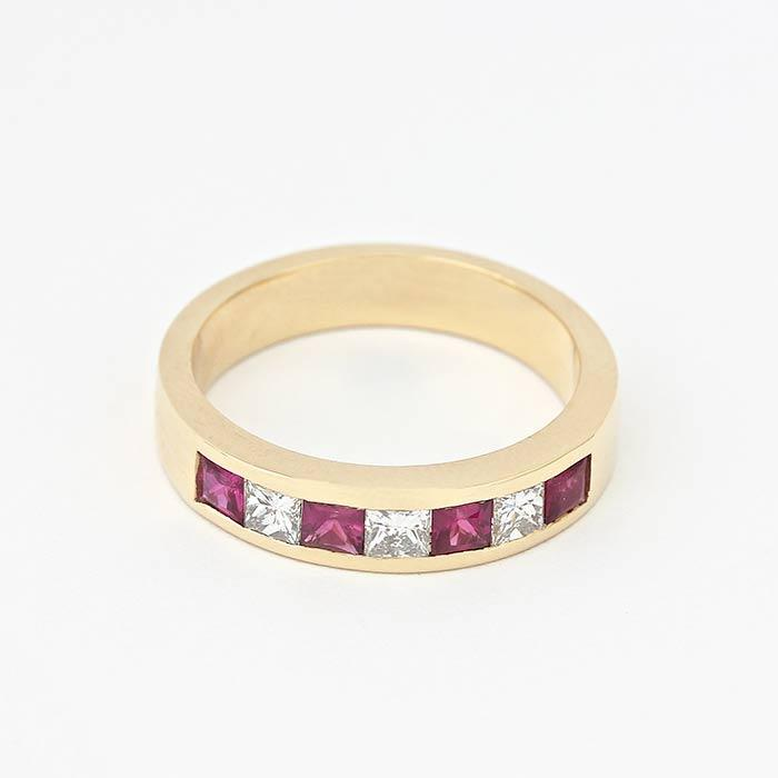 ruby and diamond half eternity ring with 4 rubies and 3 diamonds in a channel setting all in 18 carat yellow gold