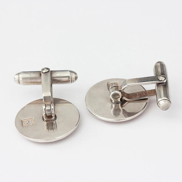 a silver pair of cufflinks with a roman wheel design satin finish