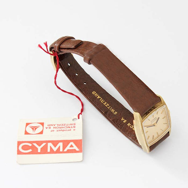 a ladies CYMA wrist watch with a tv shaped dial and gold case with brown leather strap and original ticket