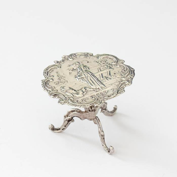 a georgian silver miniature dolls house table with decorative garden scene and 3 legs underneath dated circa 1820