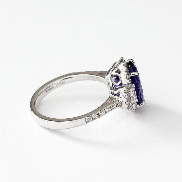 an 18ct white gold tanzanite and diamond cluster ring with diamond shoulders finger size N