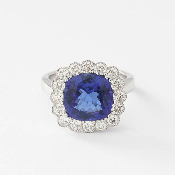 a beautiful cushion cut tanzanite and diamond cluster grain set ring in white gold