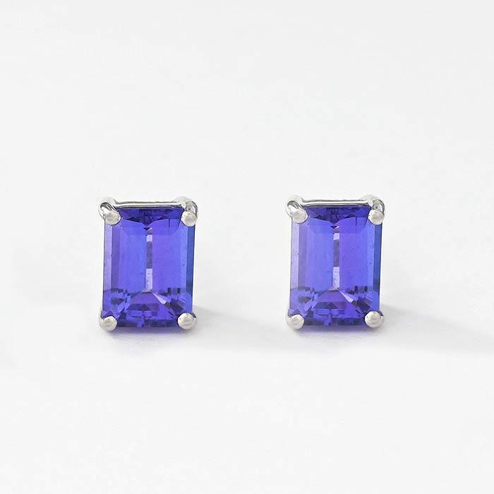 tanzanite stud earrings in 18 carat white gold in an emerald cut shape with a 4 claw setting
