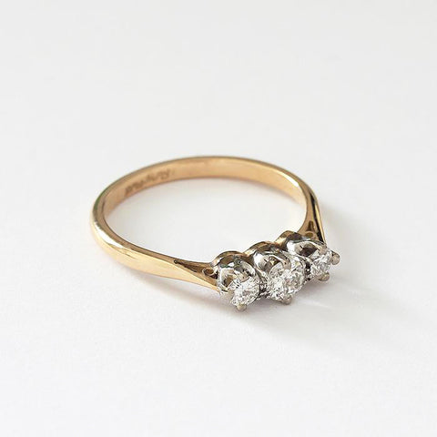 a vintage 3 stone diamond set ring with claw setting and yellow gold band