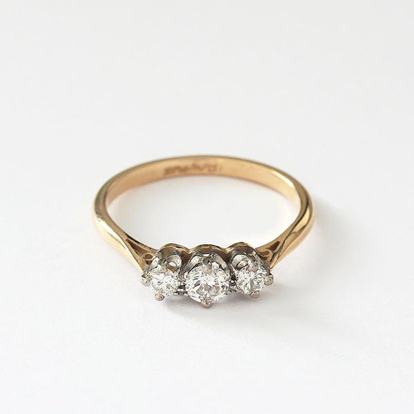 a preowned diamond 3 stone ring with a white setting and a yellow gold band