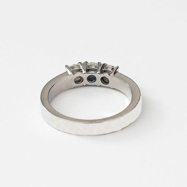 a round diamond 3 stone ring uniform in size with a claw setting and platinum band