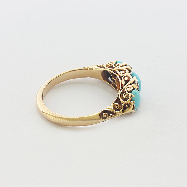 a yellow gold carved shoulders ring with turquoise diamonds
