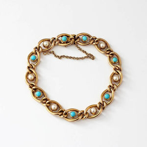 a 15 carat yellow gold link bracelet with pearls and turquoise stones and a safety chain