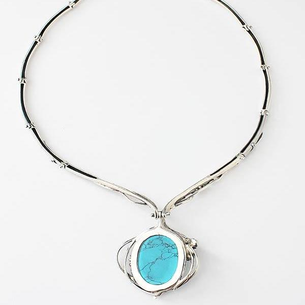 a turquoise and pearl modern large pendant necklace with a twisted wire design surround in sterling silver