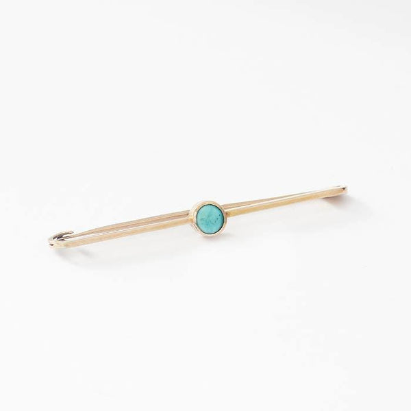 a pretty turquoise round stone yellow gold bar brooch