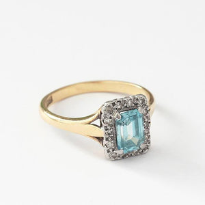a central rectangular aquamarine and surround of diamonds with a platinum setting and yellow gold band