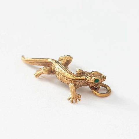 a vintage yellow gold lizard charm with green eyes enamel detail