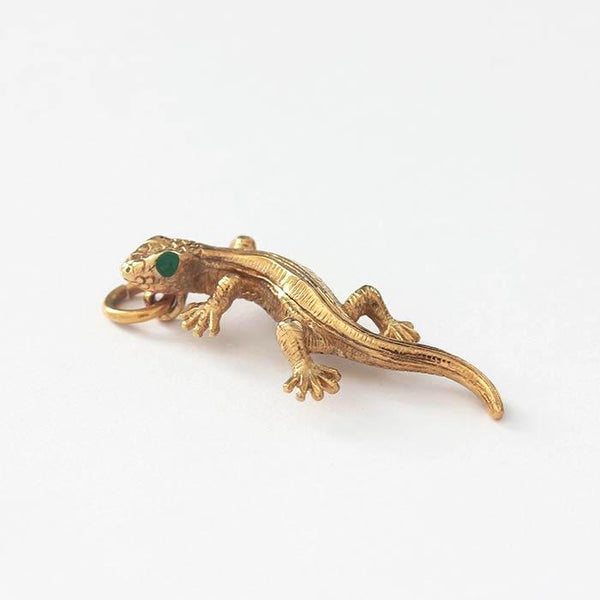 a yellow gold lizard charm with green enamel eyes
