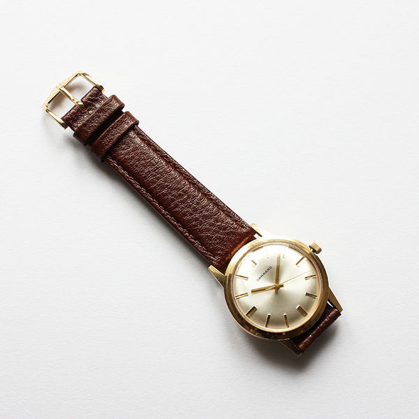 a fine quality vintage garrard mens gold watch with brown leather strap at marston barrett jewellers in lewes